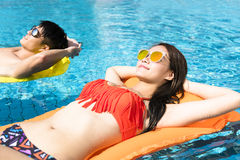 Young couple relaxing on inflatable raft. At swimming pool Royalty Free Stock Photos