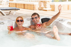 Young couple relaxing in jacuzzi pool Stock Image