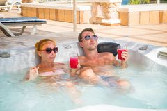 Young couple relaxing in jacuzzi pool Royalty Free Stock Images