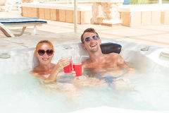 Young couple relaxing in jacuzzi pool Stock Photos