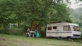 Young couple relaxing on picnic under big tree near trailer. Family vacation