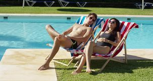 Young couple relaxing at a resort swimming pool. Sitting sunbathing on colorful deck chairs as they enjoy the hot summer sun on vacation stock footage