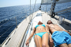 Young couple relaxing on sailing boat taking sun Royalty Free Stock Photo