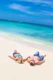 Young couple relaxing on sand tropical beach on blue sky Royalty Free Stock Photos