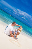 Young couple relaxing on sand tropical beach on blue sky Royalty Free Stock Image
