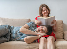 Young couple is relaxing on sofa at home and reading a book Stock Photos