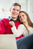 Young couple relaxing on sofa with laptop in the living room. Stock Photos