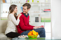 Young couple relaxing on sofa with laptop in the living room. Stock Photo