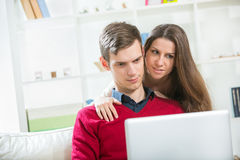 Young couple relaxing on sofa with laptop in the living room. Royalty Free Stock Images