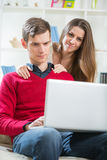 Young couple relaxing on sofa with laptop in the living room. Stock Images