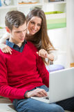 Young couple relaxing on sofa with laptop in the living room. Stock Image