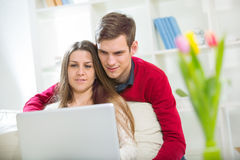 Young couple relaxing on sofa with laptop in the living room. Stock Photography