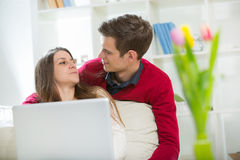 Young couple relaxing on sofa with laptop in the living room. Royalty Free Stock Photo