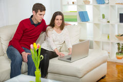 Young couple relaxing on sofa with laptop in the living room. Royalty Free Stock Photography