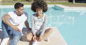 Young couple relaxing in the sun at a pool stock footage
