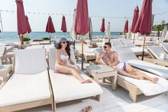 Young Couple Relaxing on Sunny Beach Resort Patio Stock Image