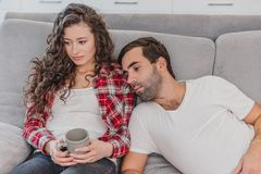 Young couple relaxing in their apartment, lying on the couch and watching the movie. The lens is the effect of glare on stock photos