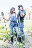 Young couple relaxing in their garden. Young couple relaxing to work in the early morning in your garden with shovel Royalty Free Stock Photo