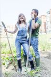 Young couple relaxing in their garden. Young couple relaxing to work in the early morning in your garden with shovel Royalty Free Stock Photography