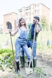 Young couple relaxing in their garden. Young couple relaxing to work in the early morning in your garden with shovel Royalty Free Stock Image