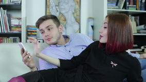 Young couple relaxing together at home and looking at a smartphone. Attractive young couple relaxing together at home and looking at a smartphone stock video footage