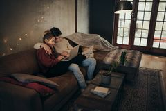 Couple relaxing with a laptop in cozy living room. Young couple relaxing together on sofa and using a laptop computer. Man and women using laptop in a cozy stock photography
