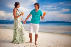 Young couple relaxing with two cocktails on sandy Stock Photos