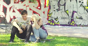 Young couple relaxing in an urban park. Sitting on the grass nuzzling and laughing affectionately together with a backdrop of colorful graffiti stock video