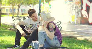 Young couple relaxing in an urban park. Sitting on the grass nuzzling and laughing affectionately together with a backdrop of colorful graffiti stock footage