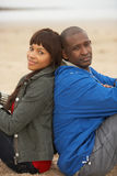 Young Couple Relaxing On Winter Beach Holiday Royalty Free Stock Photography