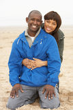 Young Couple Relaxing On Winter Beach Holiday Stock Image