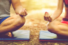 Young couple relaxing in yoga pose in green nature. Young men and women doing yoga in the sunny summer park Royalty Free Stock Images