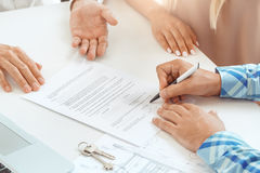 Young couple rent apartment together real estate. Young couple rent apartment together in the office signing contract Royalty Free Stock Photo