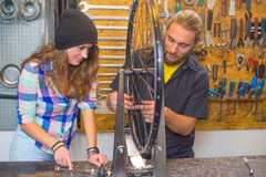 Young couple repairing bicycle in the workshop royalty free stock images