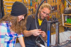 Young couple repairing bicycle in the workshop royalty free stock photos