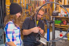 Young couple repairing bicycle in the workshop stock photos