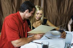 Young couple in the restaurant. Young happy couple in a restaurant, looking at the menu and deciding what to order Royalty Free Stock Images