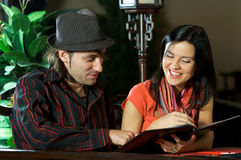 Young couple in a restaurant. The beautiful girl chooses meal from the menu of restaurant together with the man royalty free stock images