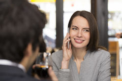 Young couple in restaurant breakfasted, woman is on the phone Royalty Free Stock Images