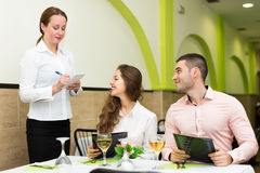 Young couple at restaurant. Cheerful waitress offering to young couple of the tasty dishes Stock Photography