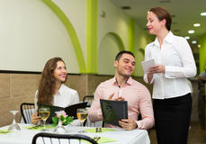 Young couple at restaurant. Cheerful waitress offering to young couple tasty dishes Stock Photos