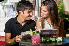 Young couple with restaurant menu at table. Stock Photo