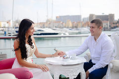 Young couple in a restaurant over marina background Stock Photo