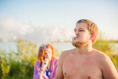 Young couple resting on the beach, smoking electronic cigarette Stock Photo