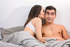 Young couple resting in bed, the girl romantic kissing boyfriend on the cheek. Stock Images