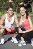 Young Couple Resting And Drinking Water After Exercise Stock Photo