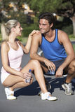 Young Couple Resting And Drinking Water After Exercise Royalty Free Stock Photography