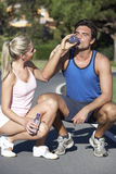 Young Couple Resting And Drinking Water After Exercise Royalty Free Stock Image