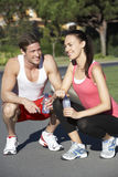 Young Couple Resting And Drinking Water After Exercise Stock Image