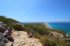 A young couple resting and enjoying crystal waters views in their way to the top of La Mola mountain in Formentera. Royalty Free Stock Photography